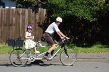 Warren and his daughter riding a tandem bike.