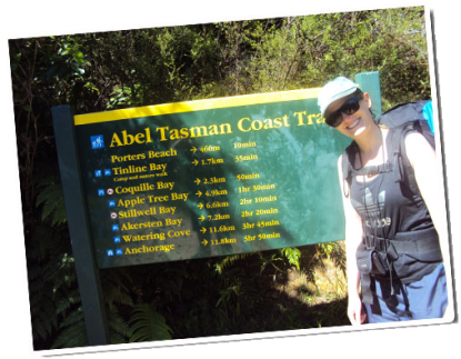 Siobhan stands in front of the DOC sign on the Abel Tasman Coastal track before an 11.8km walk.
