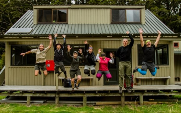 The Great Walker team jumping up in the air after reaching Iris Burn Hut.