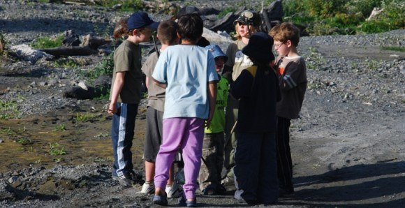 Children planning fun and games by the river in Rimutaka Forest Park.