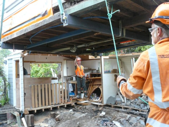 Scott's cabin is moved by crane from the earthquake crumbled cliff in Sumner.