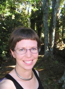 Stella McQueen standing in a forest.