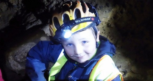 A young boy with headlight and helmet in the cave.