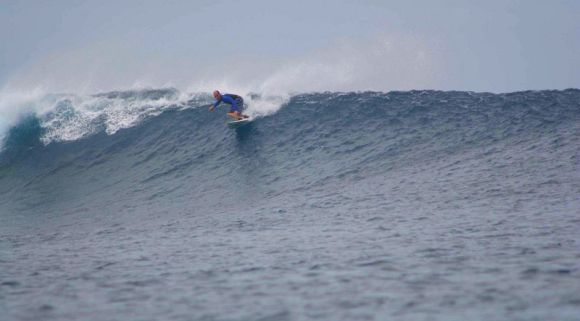 Callum surfing a wave in Fiji.