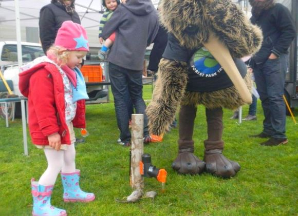 A young girl and Rimu the kiwi point to a trap and dead rats.
