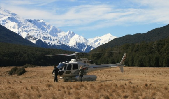 A helicopter being loaded with mountains in the background.