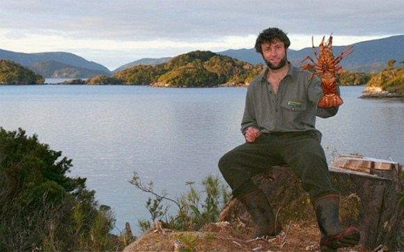 Jeff in Anchor Island harbour holding a crayfish.