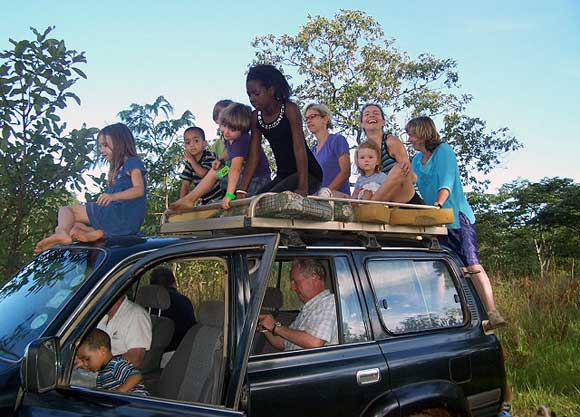 """Grab a seat and hang on for dear life. Our family trips """"bundu (bush) bashing"""" in Lusaka Zambia are legendary. I'm the one lurching off the back, my sisters atop."""