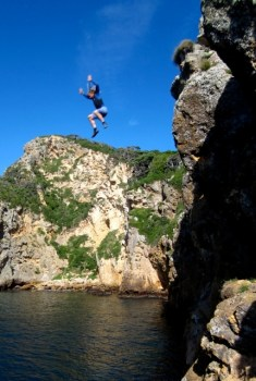 Neil Forrester jumping off Raoul Island.