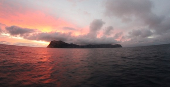 View of Raoul Island with the sun setting behind the island.