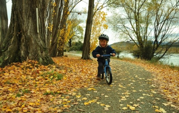 Shannon biking along amongst the leaves near Clutha River.