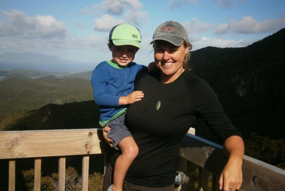 Becs holding her son on the deck of Mt Heale Hut.