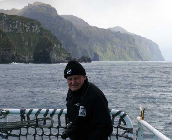 Peter Garden on the deck  of Agulhas II. Gough Island in the background.