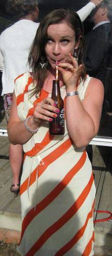 Arna in a white and orange striped dress sipping a drink with a white and orange striped straw.