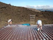 Preparing Tararua Hut roof for painting.