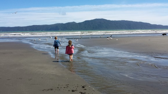 Children playing on the beach. Kapiti Island in the distance.