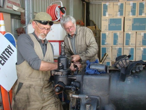 Jim with Kevin Pearce preparing the Golden Point Historic Reserve stamper battery Tangye hot bulb oil engine for restoration in the DOC workshop in Oamaru. Photo: Helen Jones .