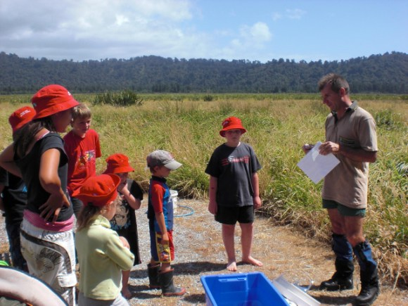 DOC ranger talking to children at a wetland.