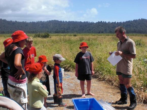 DOC ranger talking to children at a wetland.