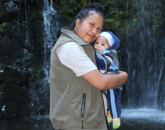 Atamaria with baby Tukutoromiro in front of a waterfall at Te Kaha.