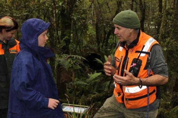 DOC ranger teaching Fenn how to hold a kiwi. Photo: Nina Mercer.