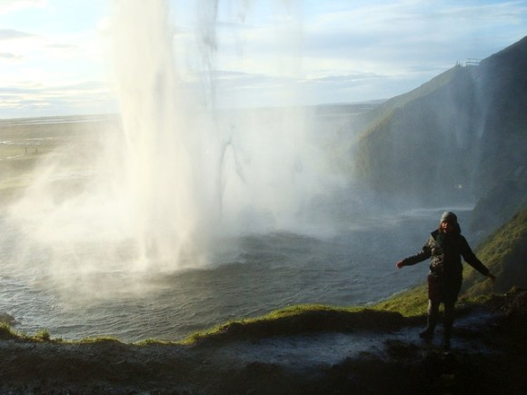 Chloe Barnes Standing behind the Seljalandsfoss waterfall in Iceland.