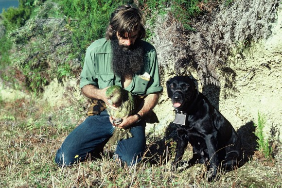 Gary Aburn holding a kākāpō with dog Mandy.
