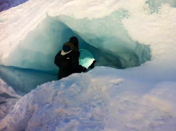 Exploring a compression cave at Fox Glacier.