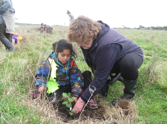 Helen and a child planting a tree at Ocean Mail Scenic Reserve.