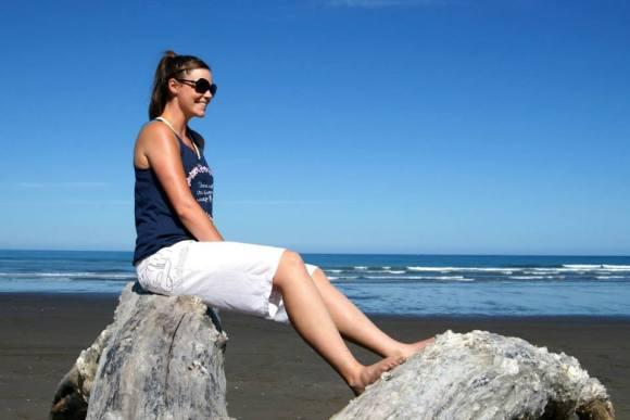 Karlene sitting on a rock at Himatangi beach.
