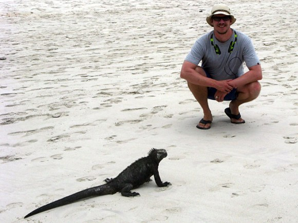 Peter beside a marine iguana on a beach in Galápagos