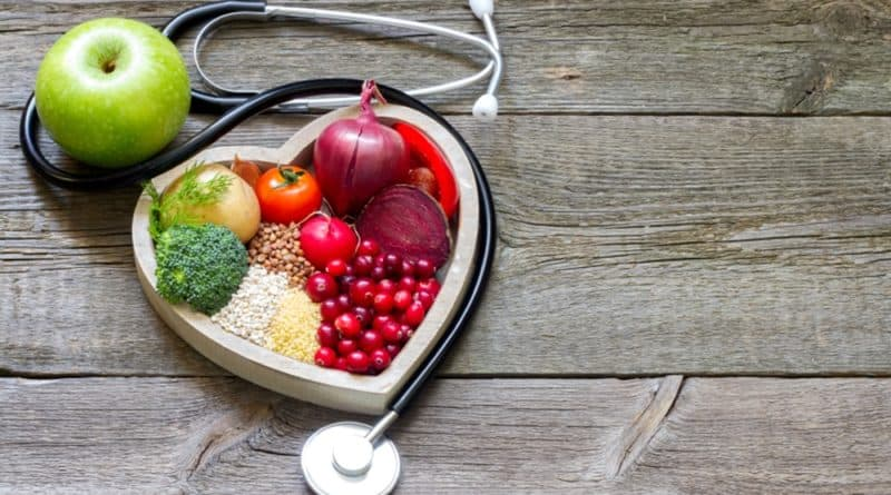 Imagem de uma mesa com grãos, legumes e verduras grupados num prato em formato de coração indicando cuidados com a alimentação