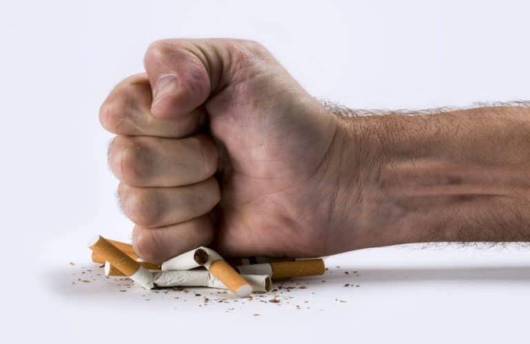Uma mão masculina amassando um amontoado de cigarro