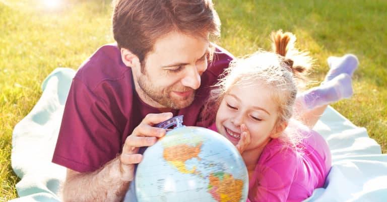 Um pai e sua filha deitados na grama olhando para um globo terrestre. O pai planeja viajar com crianças