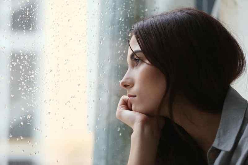 Uma mulher olhando pela janela, com o semblante triste, demonstrando a importância dos cuidados com a saúde mental