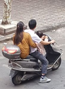 Moped with husband, wife, and child.