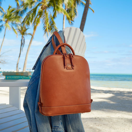 Dooney & Bourke backpack on the back of a beach chair.