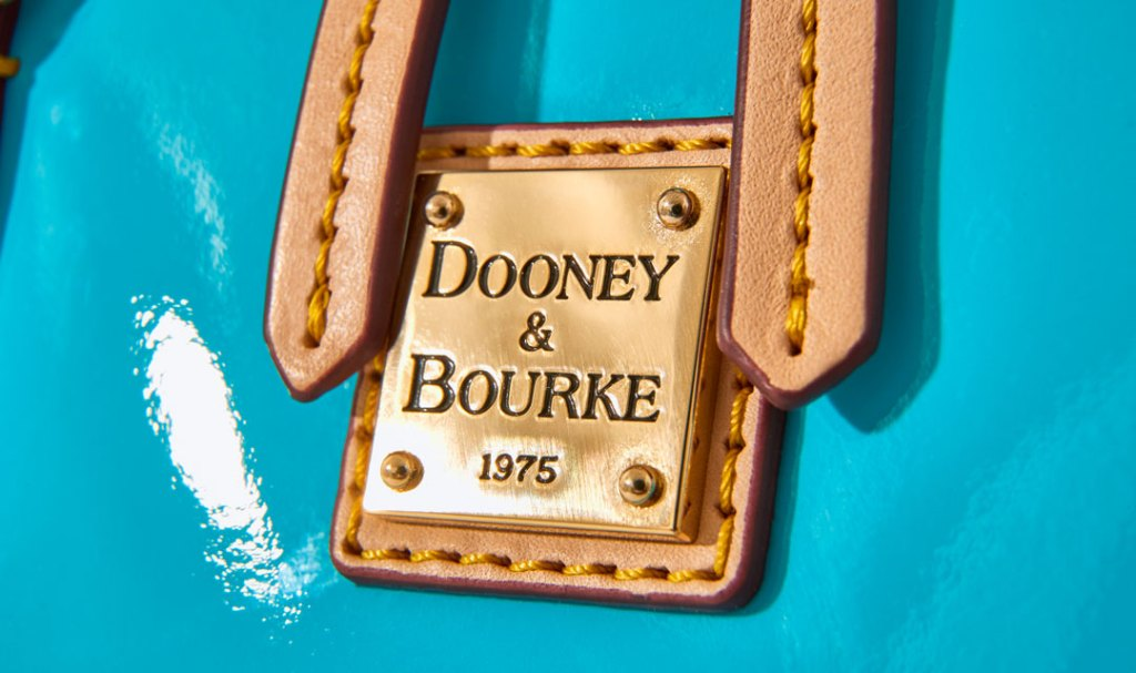 Gold-plated Dooney & Bourke logo on a blue patent leather bag.