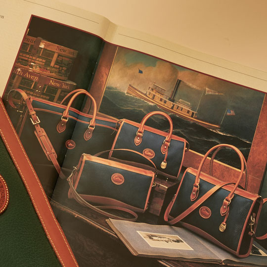 An old catalog opened to a page showing handbags from an old Nylon Collection.