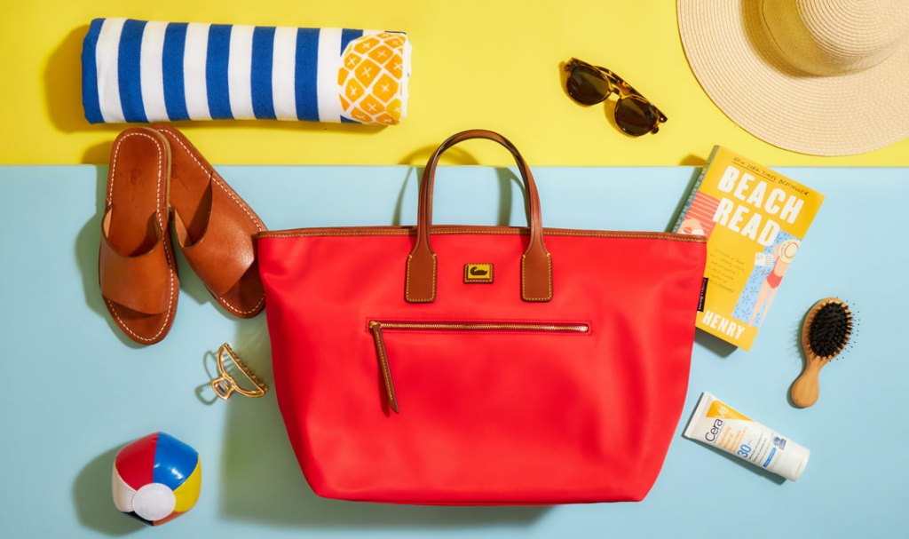 A red Wayfarer tote surrounded by a rolled up towel, sunglasses, hairbrush, sunscreen, and a book.