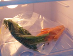 Carrots in a plastic bag in the fridge.