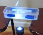 A plastic container between two chairs with a torch shining up beneath the container.