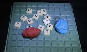 Upwords board, tiles with letters on them, two balls of plasticine.