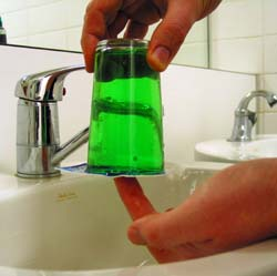 Inverted glass containing green water, with a card pressed beneath to keep the water in.