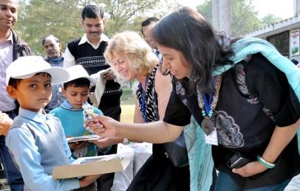 Dr Anu Kumar giving a child an Australian souvenir.