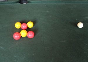 Six coloured balls form two v shapes pointing at each other.