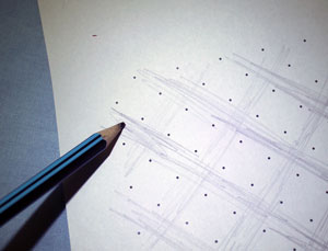 A square grid. Someone is shading lines in pencil.