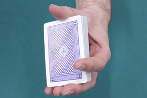 Someone is holding a deck of cards between their fingers and thumb.