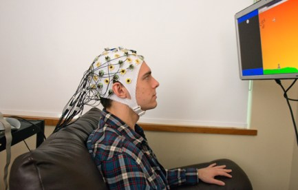 Man with a EEG on his head recording brain activity. He is looking at a screen.