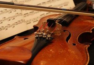 A violin near some sheet music.